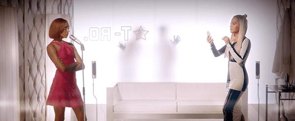 Rita Ora, que é um fantoche grande indústria está vestindo dualista vestido padrão quadriculado (indicando que ela é um escravo da indústria).  Ela é, aparentemente, muito encantado com ela mesma para julgar o cantor bem na frente dela.