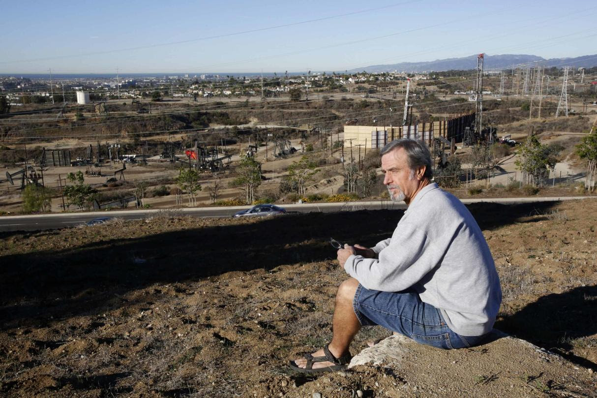 Homeowner Gary Gless sits on a hill in his neighborhood overlooking drilling wells in Los Angeles