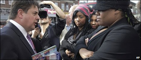 British National Party leader Nick Griffin (left) talks to local resident Suzan Olivacchi (right) as her daughters look on during a campaign tour in Dagenham