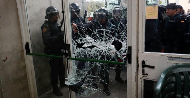La Policía destroza la puerta del colegio electoral donde tenía que votar Carles Puigdemont./ REUTERS