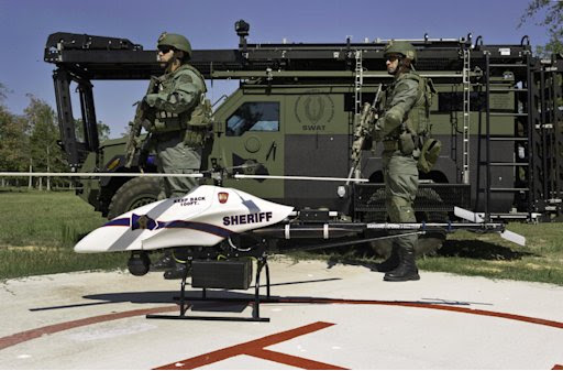This Sept. 2011 photo provided by Vanguard Defense Industries, shows a ShadowHawk drone with Montgomery County, Texas, SWAT team members. Civilian cousins of the unmanned military aircraft that have been tracking and killing terrorists in the Middle East and Asia are being sought by police departments, border patrols, power companies, news organizations and others who want a bird's-eye view. (AP Photo/Lance Bertolino, Vanguard Defense Industries)
