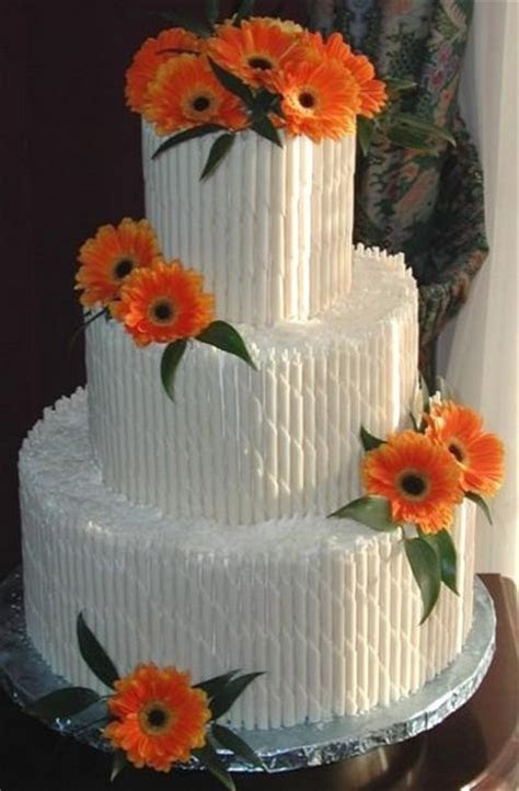 Quill wedding cake with bright orange flowers