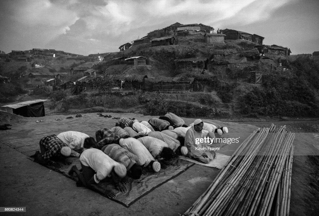 COX'S BAZAR, BANGLADESH - SEPTEMBER 25: Rohingya refugees pray at the site where they are building a new mosque at the sprawling Balukali refugee camp on September 25, 2017 in Cox's Bazar, Bangladesh. More than half a million Rohingya refugees have flooded into Bangladesh to flee an offensive by Myanmar's military that the United Nations has called 'a textbook example of ethnic cleansing'. The refugee population is expected to swell further, with thousands more Rohingya Muslims said to be making the perilous journey on foot toward the border, or paying smugglers to take them across by water in wooden boats. Hundreds are known to have died trying to escape, and survivors arrive with horrifying accounts of villages burned, women raped, and scores killed in the 'clearance operations' by Myanmar's army and Buddhist mobs that were sparked by militant attacks on security posts in Rakhine state on August 25, 2017. What the Rohingya refugees flee to is a different kind of suffering in sprawling makeshift camps rife with fears of malnutrition, cholera, and other diseases. Aid organizations are struggling to keep pace with the scale of need and the staggering number of them - an estimated 60 percent - who are children arriving alone. Bangladesh, whose acceptance of the refugees has been praised by humanitarian officials for saving lives, has urged the creation of an internationally-recognized 'safe zone' where refugees can return, though Rohingya Muslims have long been persecuted in predominantly Buddhist Myanmar. World leaders are still debating how to confront the country and its de facto leader, Aung San Suu Kyi, a Nobel Peace Prize laureate who championed democracy, but now appears unable or unwilling to stop the army's brutal crackdown.