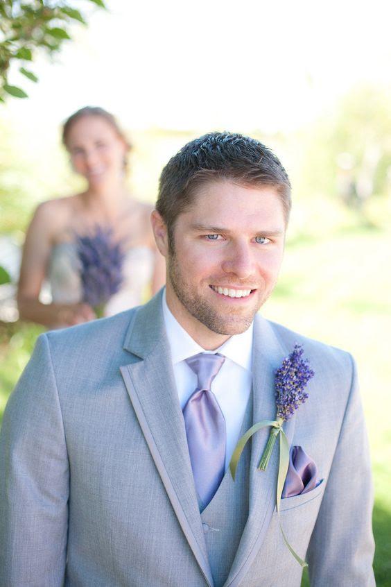 der Bräutigam trägt einen leichten grauen Anzug mit Lavendel Krawatte und ein Lavendel-boutonniere