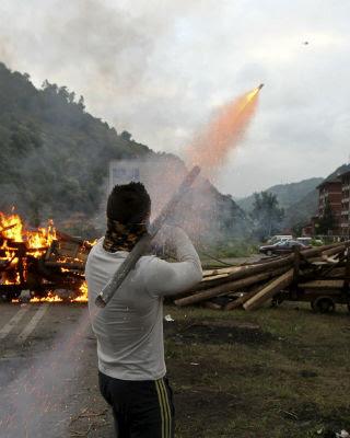Un Mineros lanzan cohetes desde la barricada colocada esta mañana en el pozo Santiago de Aller.