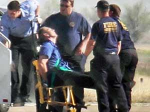 Piloto deixa a aeronave e é levado para uma clínica. (Foto: Steve Douglas / AP Photo)
