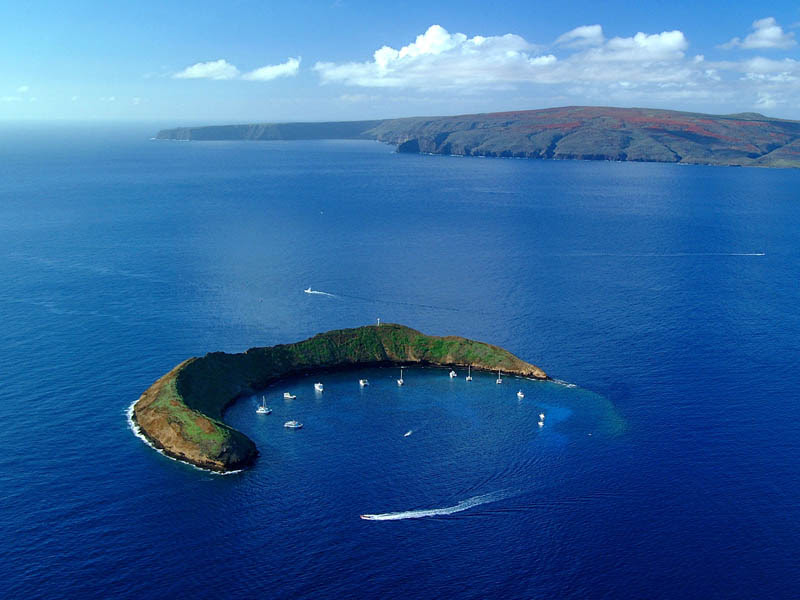 sail boats inside the crescent shaped crater of Molokini in Maui, Hawaii