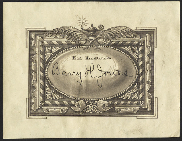 engraved bookplate : ornate striped ribbon border topped by crossed quills