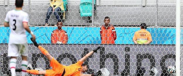Edin Dzeko's shot goes beyond the despairing dive of Iran goalkeeper Alireza Haghighi