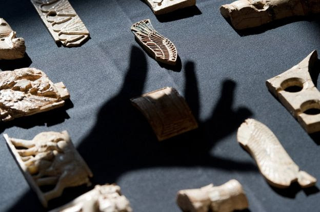 Shadow of hand over Assyrian objects on a table