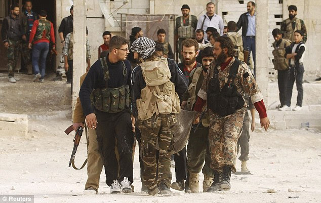 Loss: Soldiers carry the body of a fellow rebel who was killed near Aleppo International airport after clashing with Assad's forces