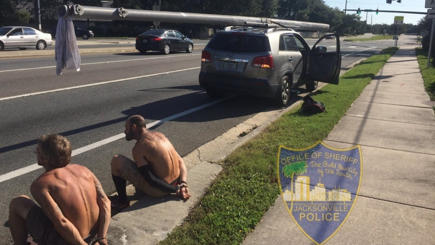 Two men were arrested Wednesday after an officer found a utility pole strapped to the top to a vehicle in Jacksonville.