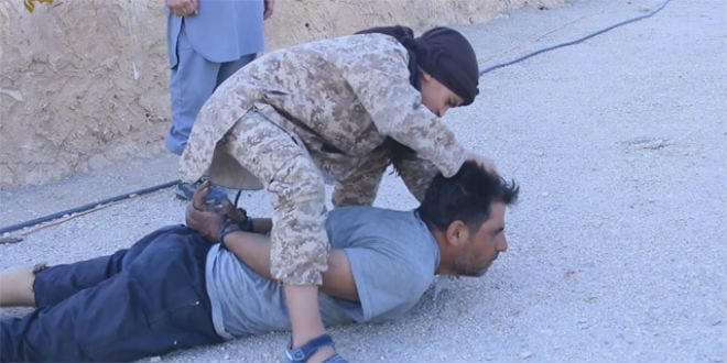 Screenshot from an ISIS video showing a young child beheading an ISIS prisoner.