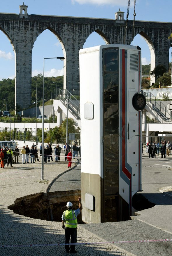 in-november-2003-rescue-workers-had-to-remove-this-bus-with-a-crane-after-it-fell-into-a-lisbon-portugal-street