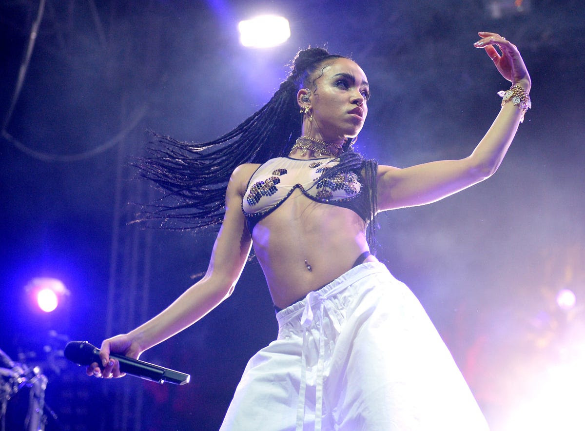 Singer-songwriter FKA Twigs whipped her hair back and forth as fiancé Robert Pattinson watched nearby.