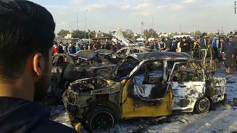 A burned-out car sits at the site of a deadly bombing Thursday in Baghdad.