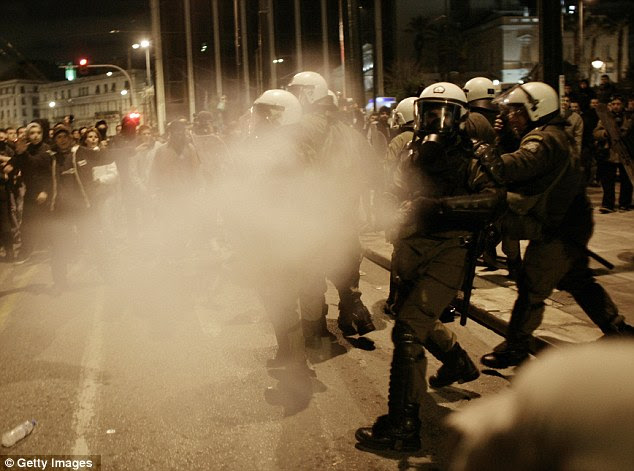 Storm: Riot police spray tear gas during the demonstration involving 3,000 people in Syntagma Square last night - a week after a much larger protest