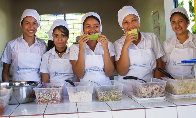 Students of the Pepenance District School in the municipality of Atiquizaya, in western El Salvador, pose for pictures in front of one of the nutritious daily meals offered to the students, which are made with products from local farmers. Credit: Edgardo Ayala / IPS