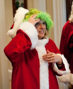 Jill Biden removing her mask after going as the Grinch to a White House holiday party.