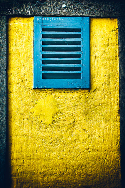Tiny window on yellow wall with closed shutter