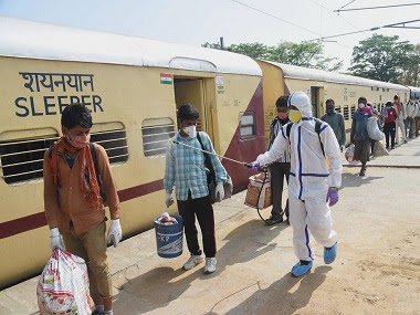 A health worker sanitizes migrants who have arrived from Jaipur by 'Shramik Special' train at Danapur junction in Patna. PTI