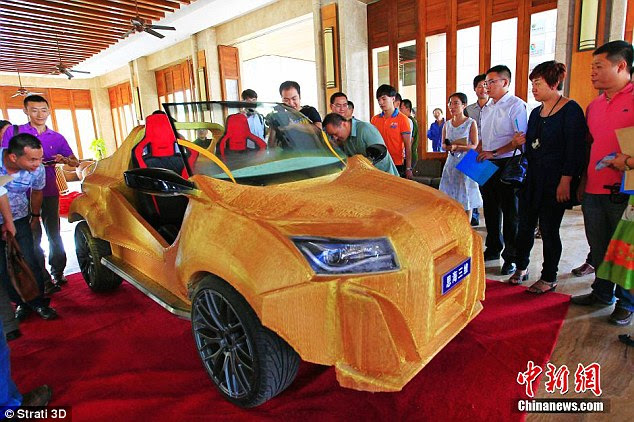 Onlookers watch the unveiling of China's debut 3D-printed car Shuya, capable of reaching speeds of up to 40 km/hr