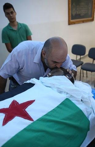 O sírio Amer Masarani beija o corpo do amigo (Foto: Gabriel Chaim/G1)