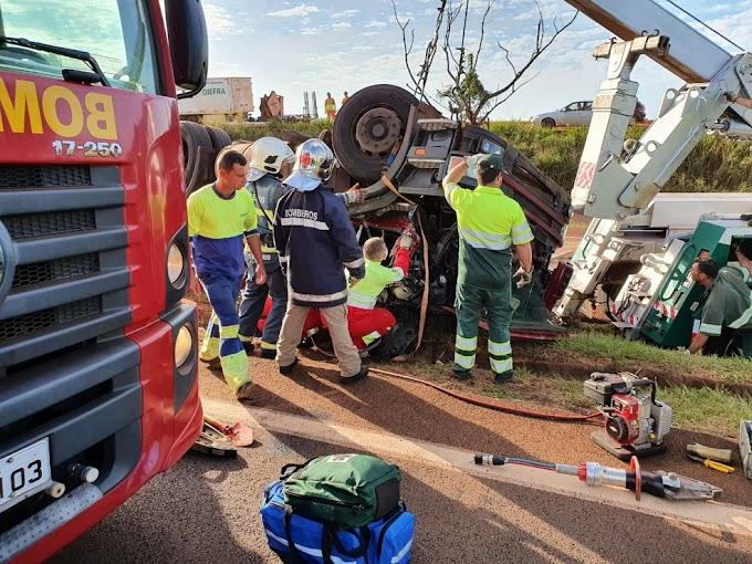 PRESO AS FERRAGENS: Caminhão tomba e cabine e içada por guincho para socorrer motorista