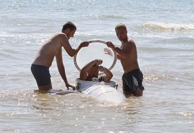 O inventor entra no submarino com a ajuda de dois assistentes (Foto: Gleb Garanich/Reuters)