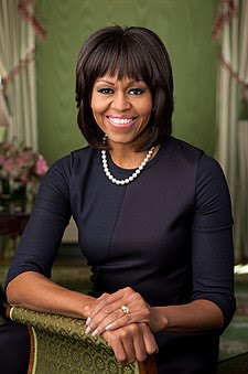Mrs Obama facing forward, smiling, clad in black dress and single strand pearl necklace resting bare right forearm and both hands on a brocaded sofa armrest.