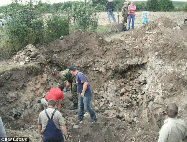 Volunteers dig within the crater, exhuming the fateful planes remains