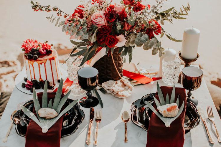 Die Wüste Picknick-Tisch war mit schwarzen Platten, große Blätter, gold Besteck und Becher schwarz