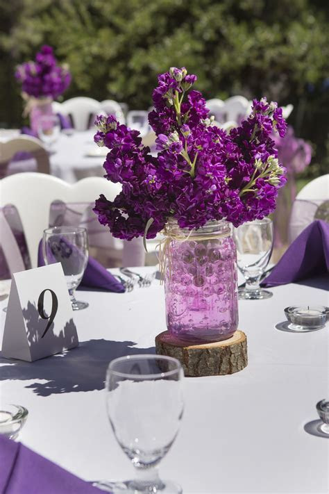 Simple purple stock centerpieces in mason jars w/raffia