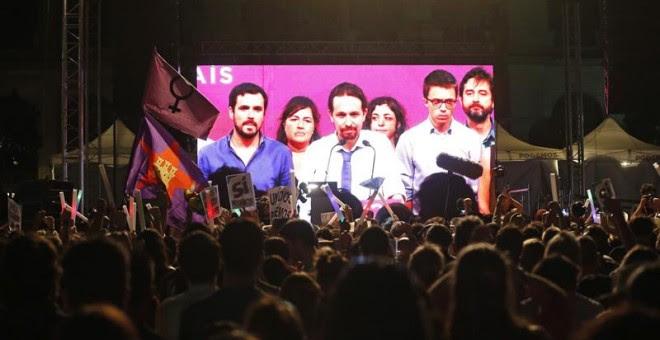 Simpatizantes de Unidos Podemos escuchan las declaraciones de su líder Pablo Iglesias (c. en la pantalla) durante su comparecencia ante la prensa tras conocer los resultados de las elecciones generales celebradas en España, hoy en la plaza del museo Reina