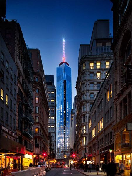 Under the night sky, the 1 World Trade Center's (1 WTC) antenna spire glows above New York City.