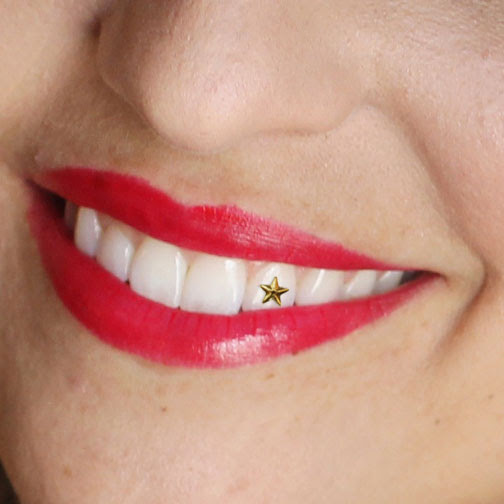 Smiling woman wearing red lipstick with a gold star tooth gem
