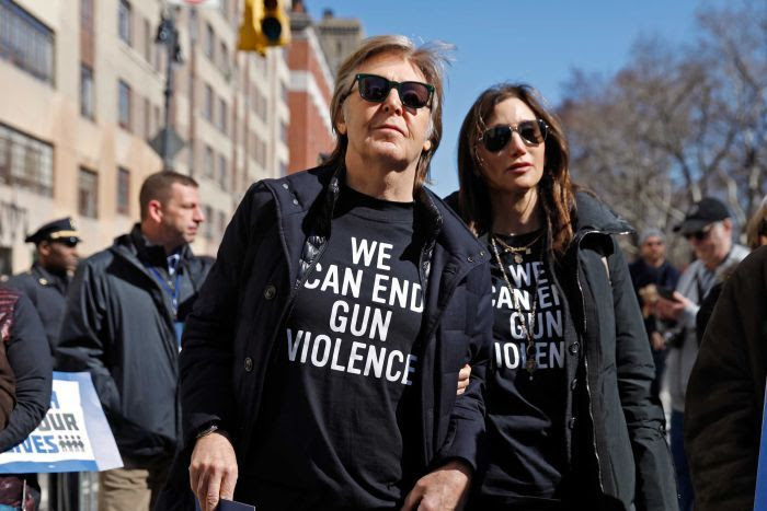 Paul McCartney and a woman are seen in a rally wearing 'we can end gun violence' tshitrts.