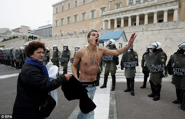 Furious: Ένας διαδηλωτής φωνάζει συνθήματα σε αντίθεση με τις περικοπές μπροστά από τη γραμμή των ΜΑΤ