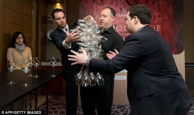 Phillip, 43, pictured getting a helping hand from two judges as he broke the world record, learnt his art working as a sommelier at the Savoy and the Ritz in London