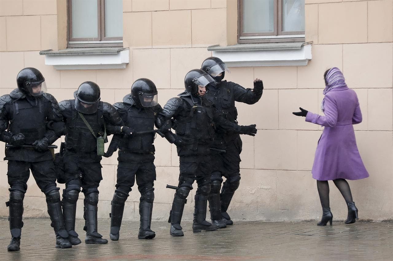 A woman argues as Belarus police block a street during an opposition rally in Minsk, Belarus, Saturday, March 25, 2017. A cordon of club-wielding police blocked the demonstrators' movement along Minsk's main avenue near the Academy of Science. Hulking police detention trucks were deployed in the city center.