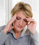 A middle aged woman holding her head suffering from a headache.