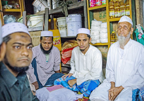 Rohingya men sit in a shop in Sittwe's Aung Mingalar neighbourhood. (Kaung Htet/The Myanmar Times)