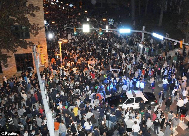 Unrest: Penn State University students take to the streets and chanted Mr Paterno's name after hearing the famed coach had been sacked