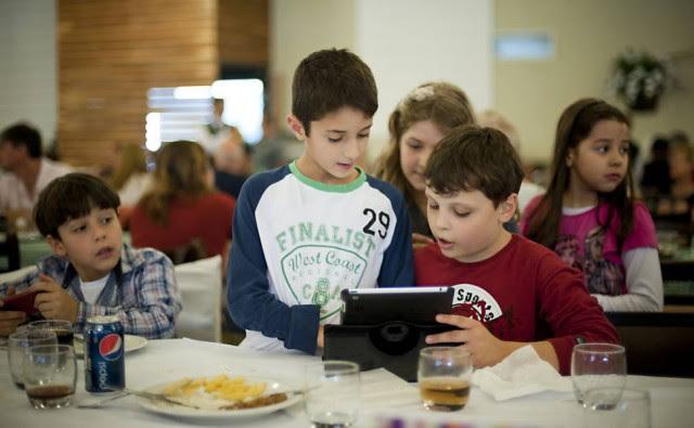 Amigos brincam com tablet no restaurante; no ano passado, nos Estados Unidos, 44% das crianças diziam querer um tablet no Natal. Foto: Isadora Brant / Folhapress