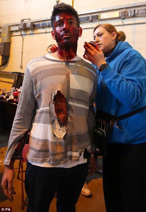 Γραφικό: Ένας ηθοποιός έχει μια ανοικτή πληγή στο στήθος ζωγραφισμένο πάνω του πριν από την άσκηση αντιμετώπισης καταστάσεων έκτακτης ανάγκης
