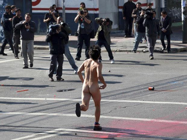 Manifestante corre nu durante protesto antigoverno no Chile neste sábado (21). Manifestação aconteceu nos arredores do Congresso, enquanto presidente Sebastian Piñera transmitia mensagem anual à nação (Foto: Ivan Alvarado/Reuters)