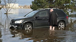 Gary MacDonald wades through a flooded parking lot to get to his vehicle near the St. John River on Tuesday in Fredericton.
