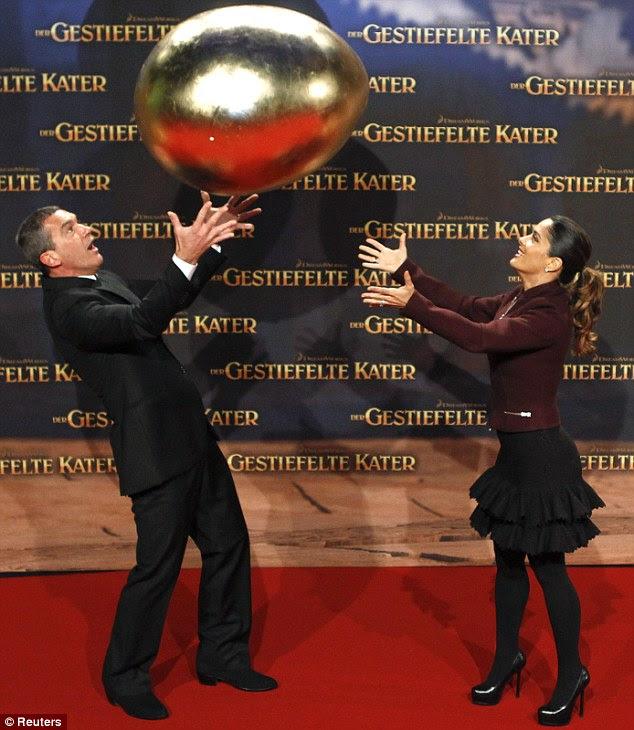 Novo para o tapete vermelho: Antonio Banderas e Salma Hayek foram fotografados brincando com um ovo gigante de ouro na estréia do Gato de Botas
