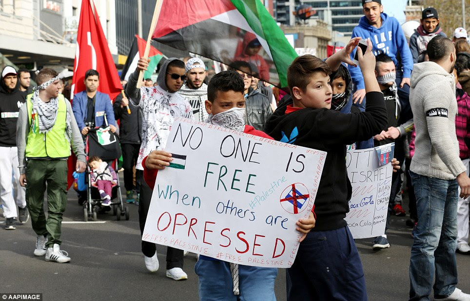 A young boy held a sign saying 'no one is free when others are oppressed' while his friend took photos of the march on his iPhone. In the background, a toddler in a pushchair was also brought to the march