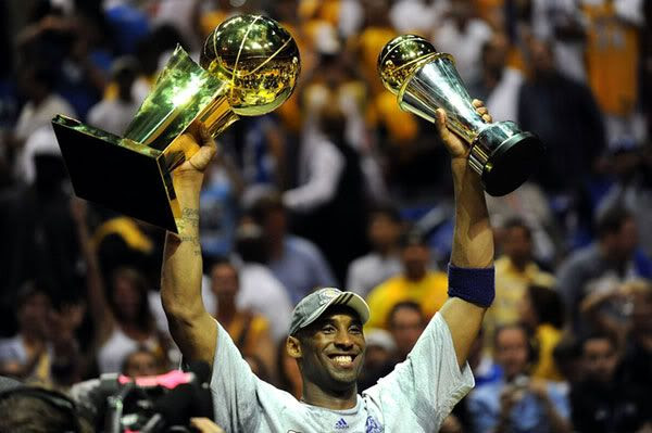 Kobe Bryant hoists up the NBA championship trophy and his Finals MVP trophy after he leads the Lakers to its 15th title, on June 14, 2009.
